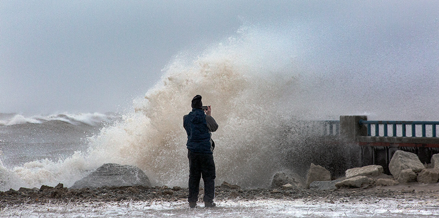Man with iPhone facing the surging surf on Milwaukee's lakefront