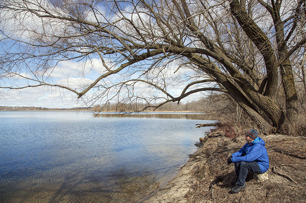 A man sitting next to the lake at Pike Lake Unit - Kettle Moraine State Forest