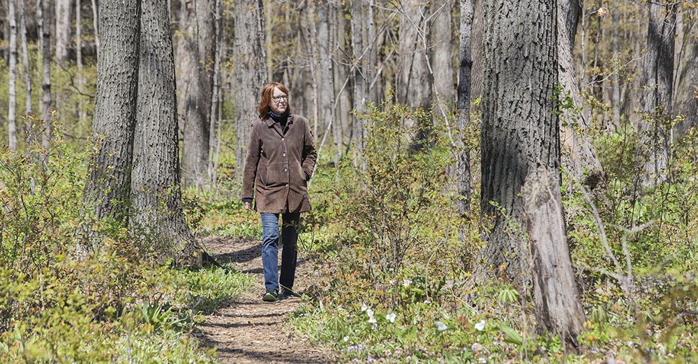 A woman walking on a woodland path in Bratt Woods