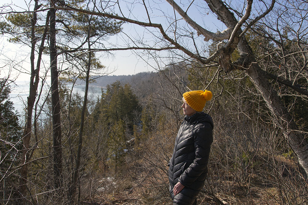 A woman overlooking Lake Michigan from a bluff top at Donges Bay Gorge Natural Area