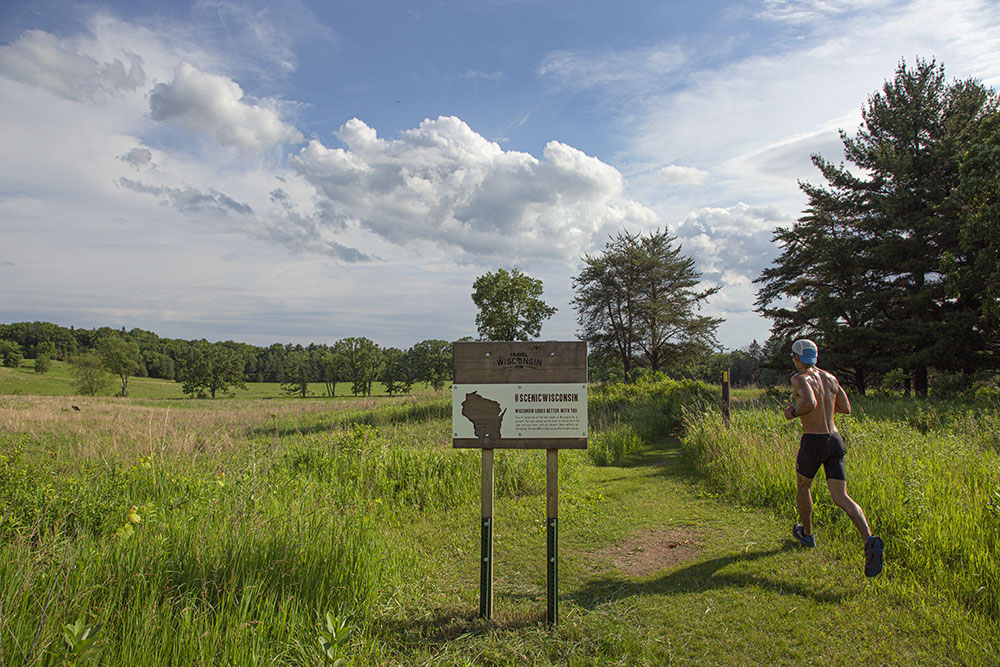 A man jogging on a trail in an open field at Lapham Peak