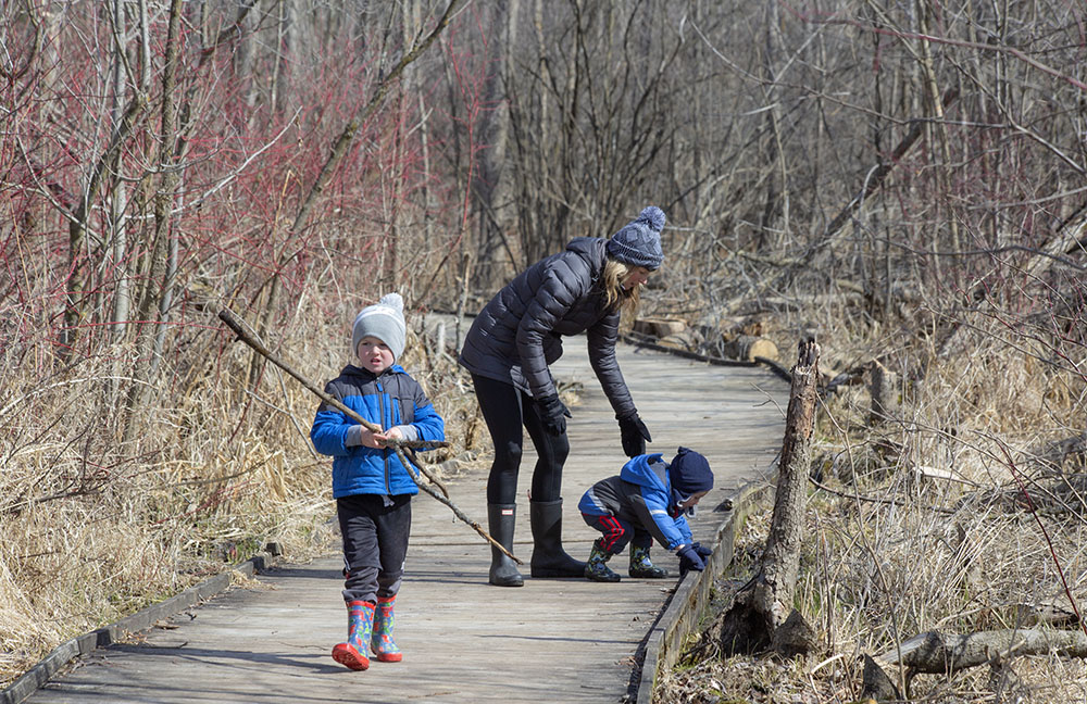 Mom and two young kids on a boardwalk at Pike Lake State Park