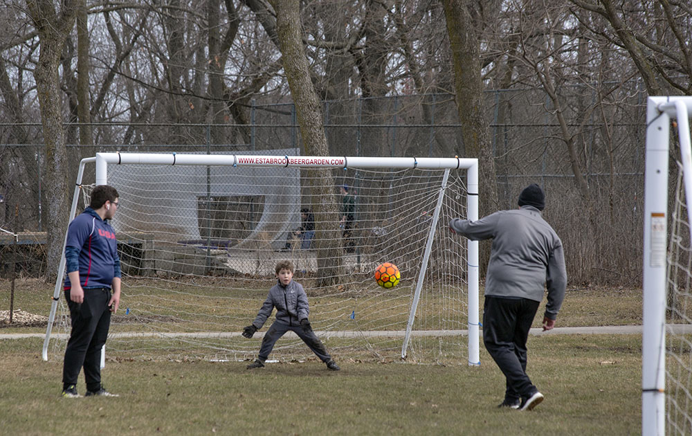 Two young men and a boy playing soccer at Estabrook Park