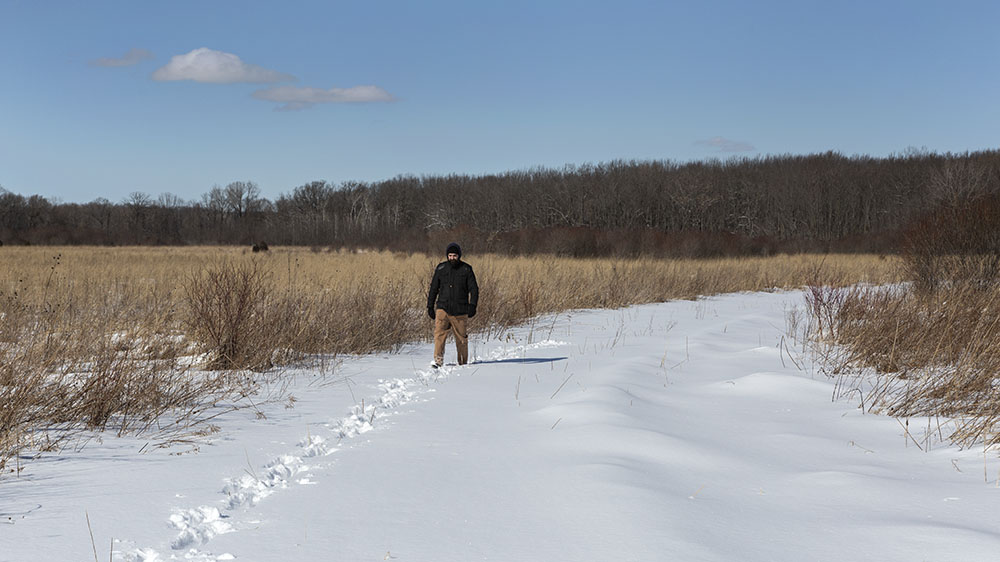 A man walking on a wide, snowy path in an open prairie at Fellenz Woods Preserve