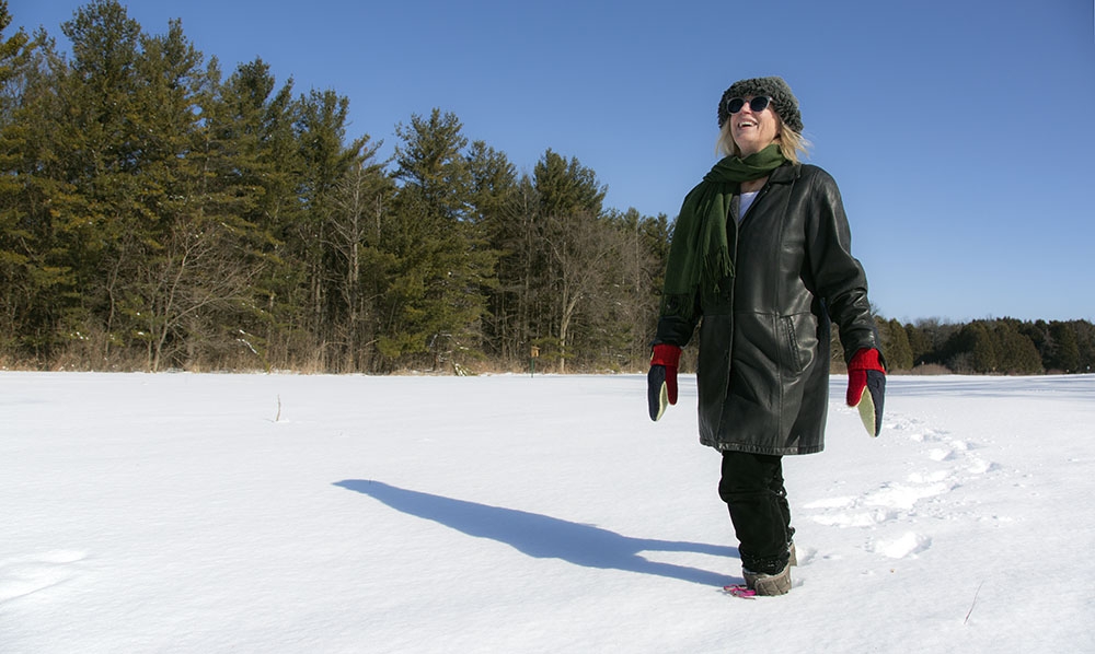 Artist in residence Tori Tasch walking in an open, snow-covered field at Schoofs Preserve