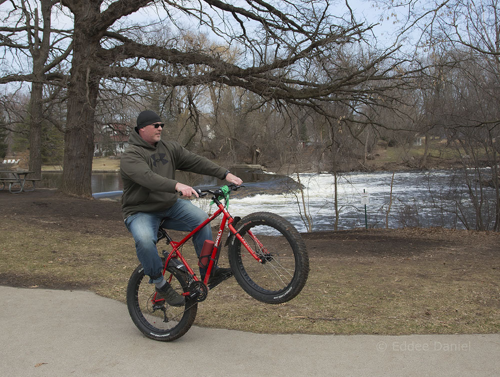 A man doing a wheelie on a fat tire bike in Kletzsch Park