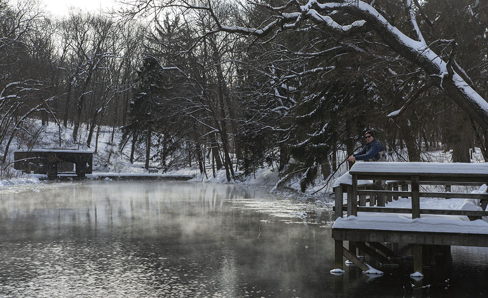 A man fishing in the pond in winter at Paradise Springs Nature Trail