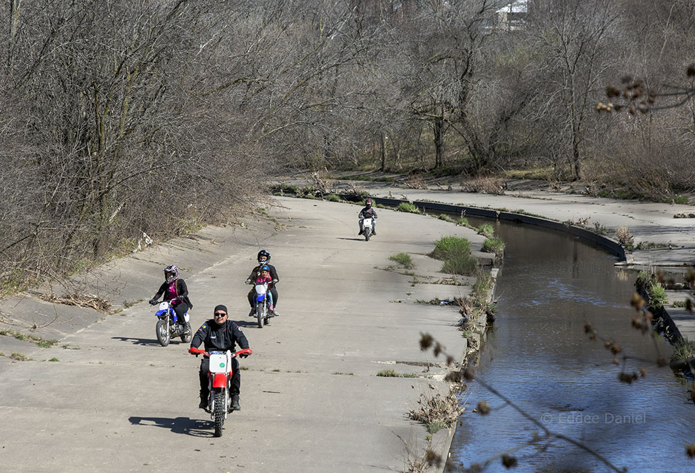 A family of motorbikes using the Kinnickinnic River as a race course.