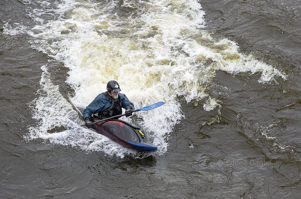 A veteran white water kayaker braves the standing waves on the Milwaukee River below the North Avenue Bridge.