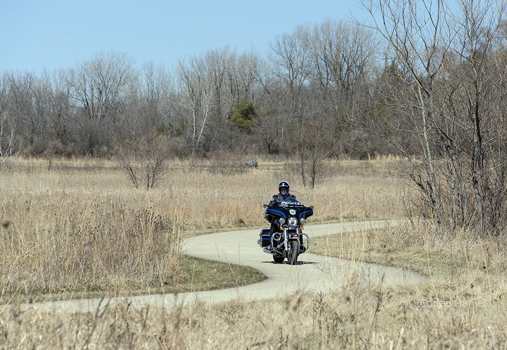 A motorcycle patrols the multi-use path in the Pike River Greenway, Mount Pleasant.