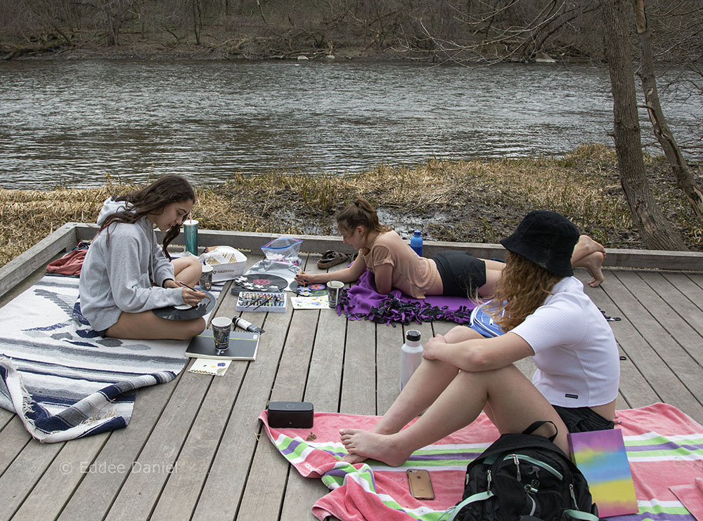 Three girls painting designs on old records in the Milwaukee River Greenway, Shorewood.