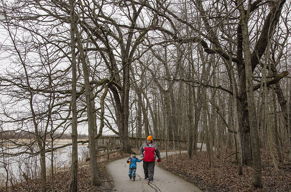 A mother with her young son on the paved riverside path at Fox River Park in Waukesha