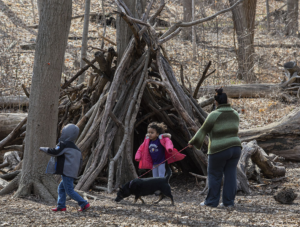 Family exploring a stick fort at Petrifying Springs Park in Kenosha.