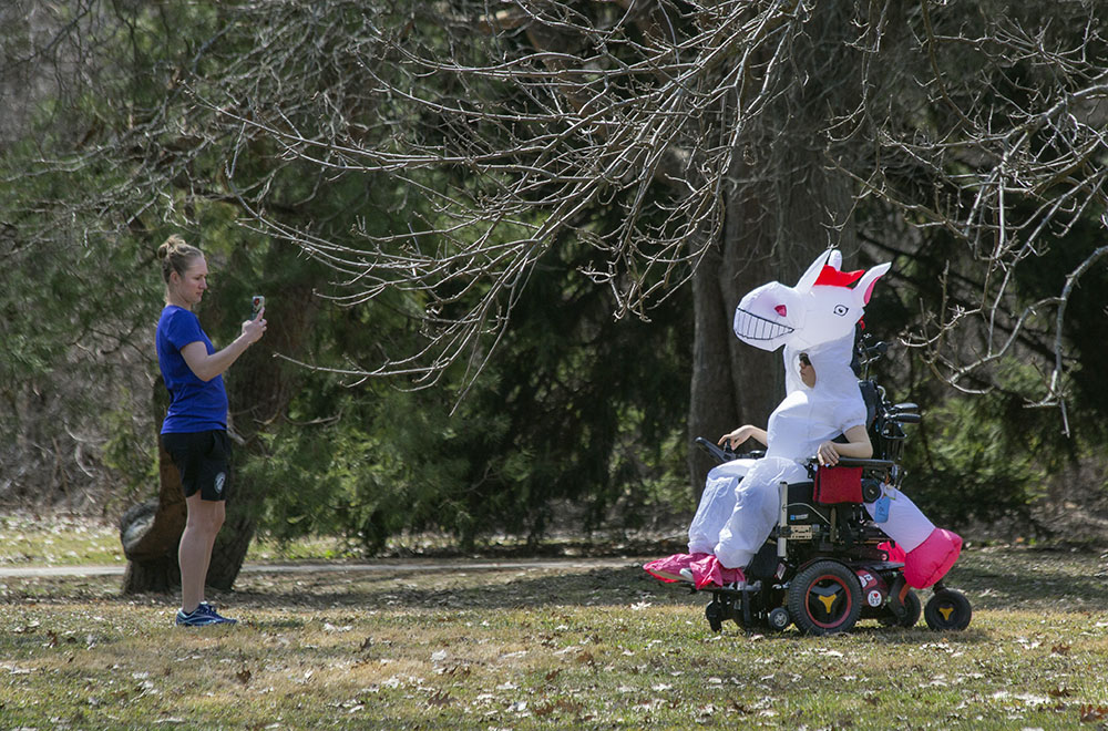 A boy in a wheelchair out enjoying the sunshine with his caretaker at Hoyt Park in Wauwatosa.