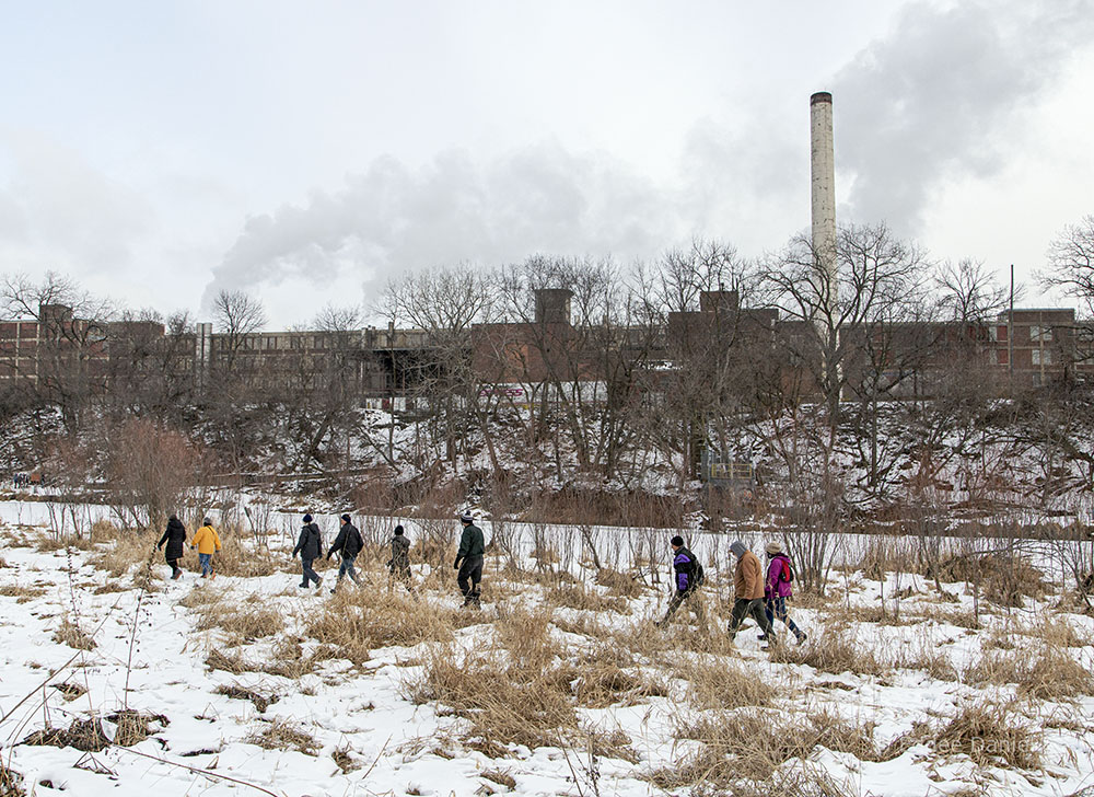 Meetup hikers on the West Bank Trail in view of Wisconsin Paperboard, a recycling plant